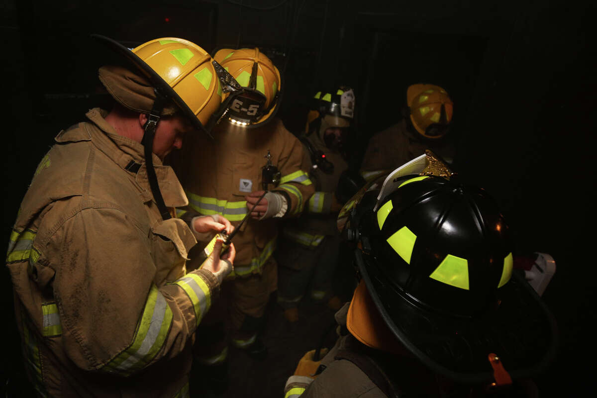 Conroe firefighters set up radios before venturing into a facility called the survival house with participants of Conroe IAFF's Fire Ops 101 on Friday, Oct. 21, 2016, at the Val Jahnke Training Facility in Houston.