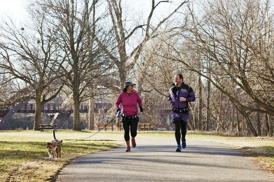 Midland residents Dan and Pamela Solomon and their beagle named Brody run near The Tridge on Sunday, Feb. 26. Photo: Theophil Syslo For The Daily News