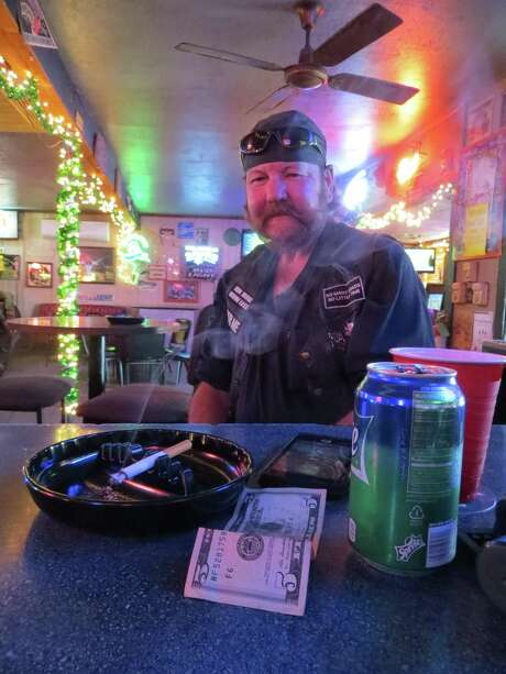 Tim Gilbreth enjoys a cigarette at the Hoity Toit Beer Jointin New Braunfels, one of the few remaining nightspots there to still allowsmoking inside. A proposal now before the city council would eliminate the exemption for bars and hospitals found in the currentmunicipal smoking ordinance, and also regulate vaping. Photo: Zeke MacCormack / Staff