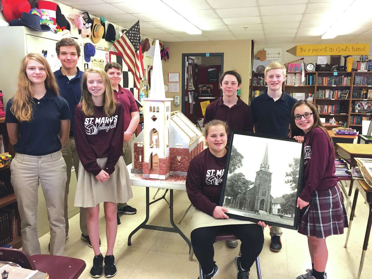 """Eighth-grade students in Debbie Caulk's class show off the model of the """"old"""" church they are building in celebration of St. Mary's 175th anniversary."""