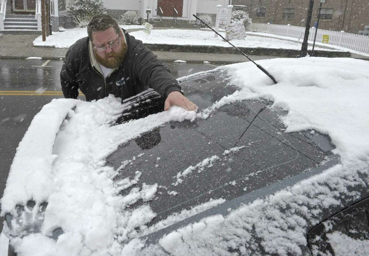 Mark Sheridan, of Bethel, clears the snow from the rear window of his car, parked on Greenwood Avenue, on Friday morning, March 10, 2017, in Bethel, Conn.