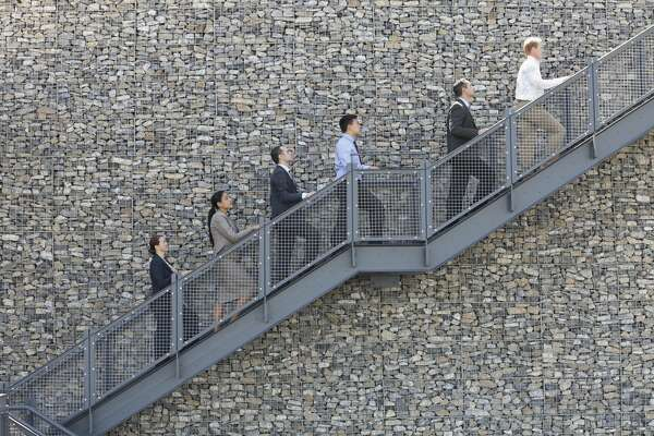 Side view of business people climbing staircase in a line
