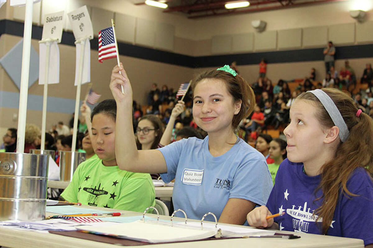 Pearland High School junior Rachel Moore, center, watches over Pearland Junior High South eighth-grader Mitchell Lester, left, and Pearland Junior High East seventh-grader Alex Bryan, right, as they answer questions during the Pearland ISD Quiz Bowl.