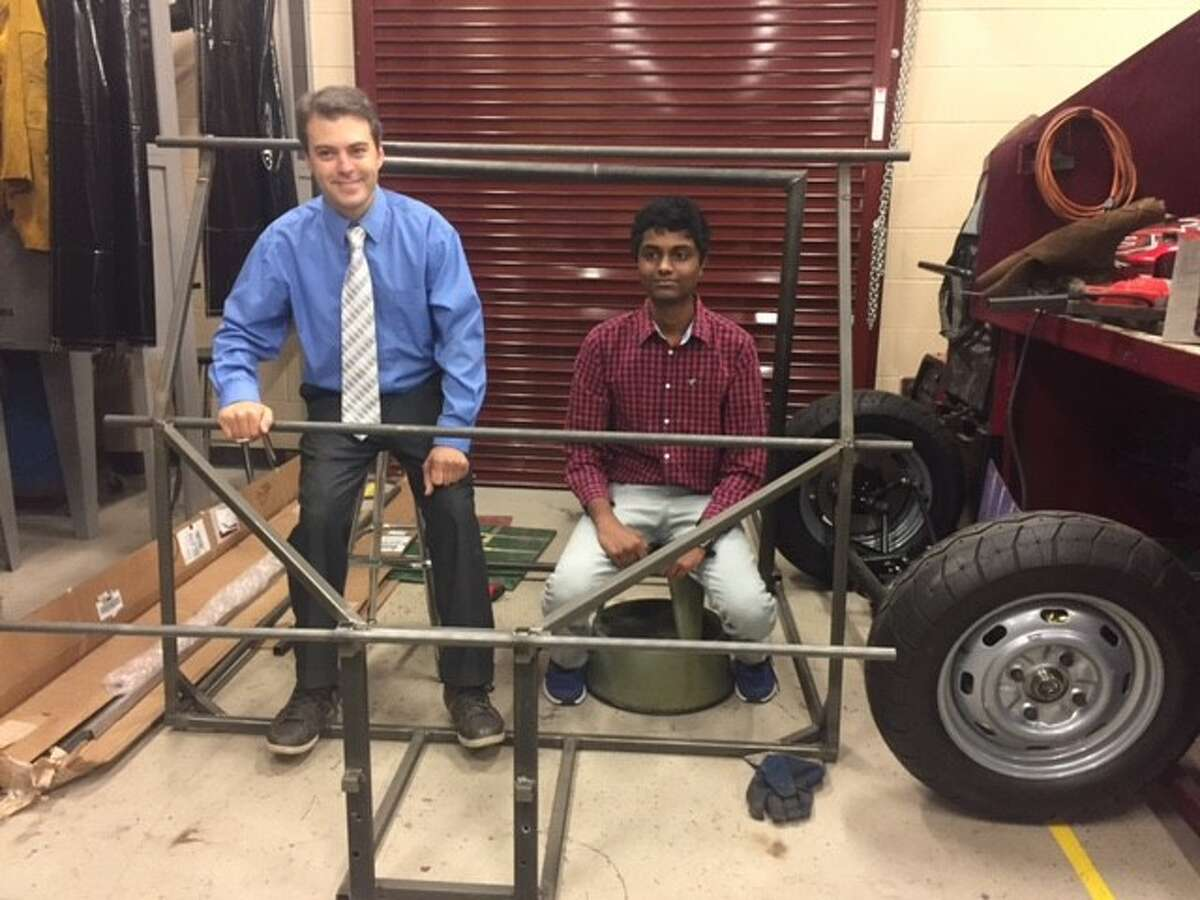 Clear Creek ISD Teacher Michael McGregor and student Santosh Balachandra assess frame of solar car to race at Texas Motor Speedway in Fort Worth this summer.