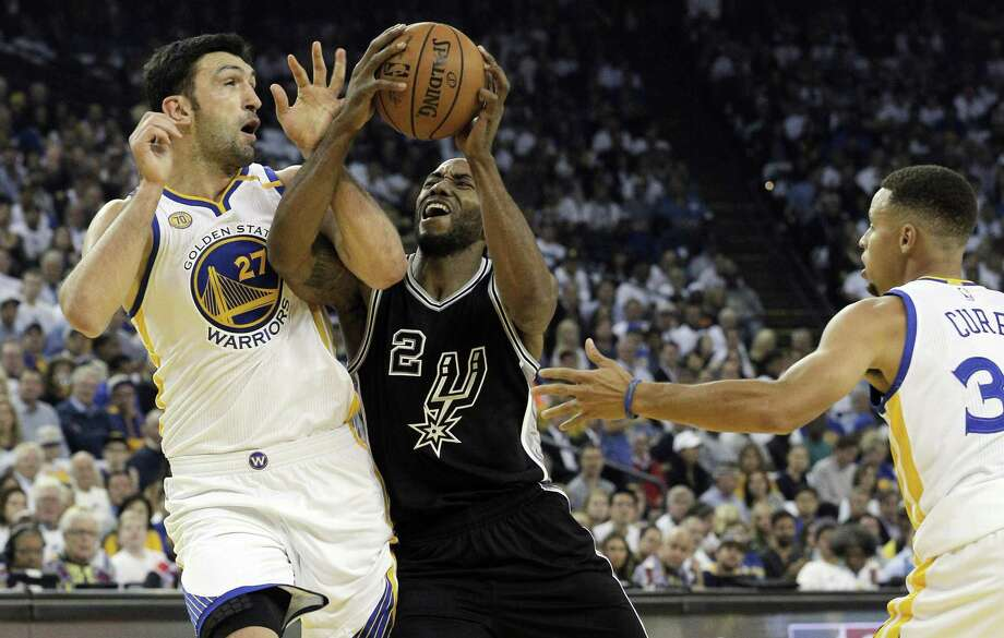 Kawhi Leonard (2) drives into Zaza Pachulia (27) in the first half as the Golden State Warriors played the Spurs in the season opener at Oracle Arena in Oakland, Calif., on Oct. 25, 2016. Photo: Carlos Avila Gonzalez /San Francisco Chronicle / San Francisco Chronicle/Carlos Avila Gonzalez