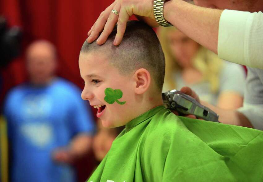 Student William Levy, 5, has his head shaved by Ryan Recupero, of Ryan Jon Salon, during the Stratfield Elementary School Fighting Molonys 9th annual St. Baldrick's Foundation head-shaving event at the school in Fairfield, Conn., on Wednesday Mar. 8, 2017. The St. Baldrick's Foundation is a volunteer-powered organization dedicated to raising money for children's cancer research.