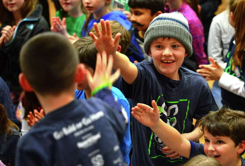 Student James McBennett, 10, at top right, reaches out to high five his buddy who is going to get his head shaved, during the Stratfield Elementary School Fighting Molonys 9th annual St. Baldrick's Foundation event at the school in Fairfield, Conn., on Wednesday Mar. 8, 2017. The St. Baldrick's Foundation is a volunteer-powered organization dedicated to raising money for children's cancer research.