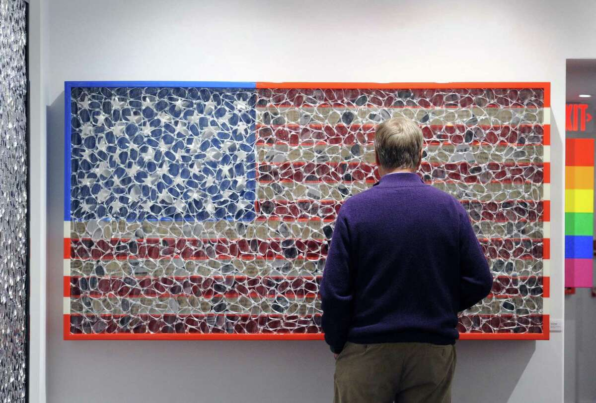 Old Greenwich resident Gunnar Klintberg views an artwork of an American Flag during a show by New York-based artist David Datuna at the Gilles Clement Gallery in Greenwich, Conn., Thursday night, March 9, 2017.