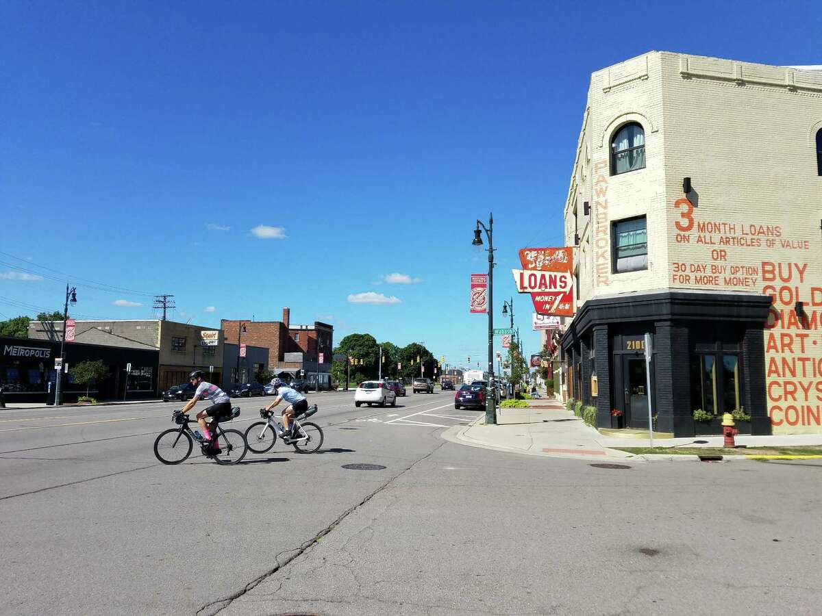 Cyclists ride past Gold Cash Gold, a popular new restaurant on a redeveloping stretch of Detroit's Corktown neighborhood.