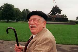 In a file photo with the Iwo Jima Memorial in the background, Pulitzer Prize winning photographer Joe Rosenthal poses for photographers Wednesday, June 28, 1995 in Arlington, Va., during a ceremony honoring photographers who lost their lives covering military conflicts around the world. Rosenthal won a Pulitzer Prize for making the photo that the Iwo Jima Memorial is modeled after. Rosenthal died Sunday, Aug. 20, 2006. He was 94. (AP Photo/Doug Mills)