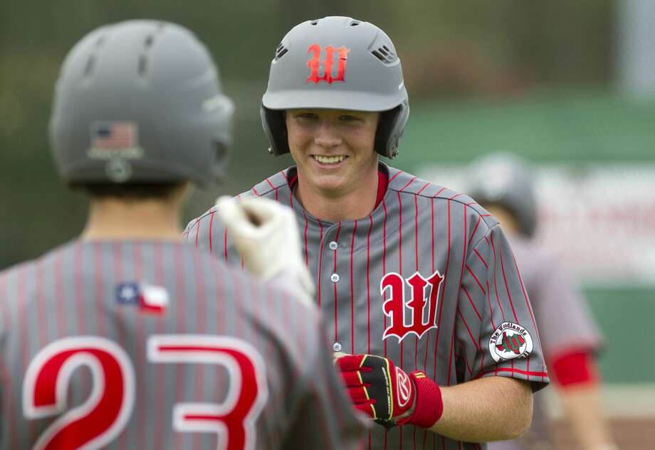 Will Swope #24 of The Woodlands smiles as he greets Drew Romo after hitting a solo home run off Keller reliever Carter Campbell (15) during the fourth inning of a high school baseball game at the Wings-N-More Classic Friday, March 10, 2017, in The Woodlands. The Woodlands defeated Keller 16-4. Photo: Jason Fochtman/Houston Chronicle