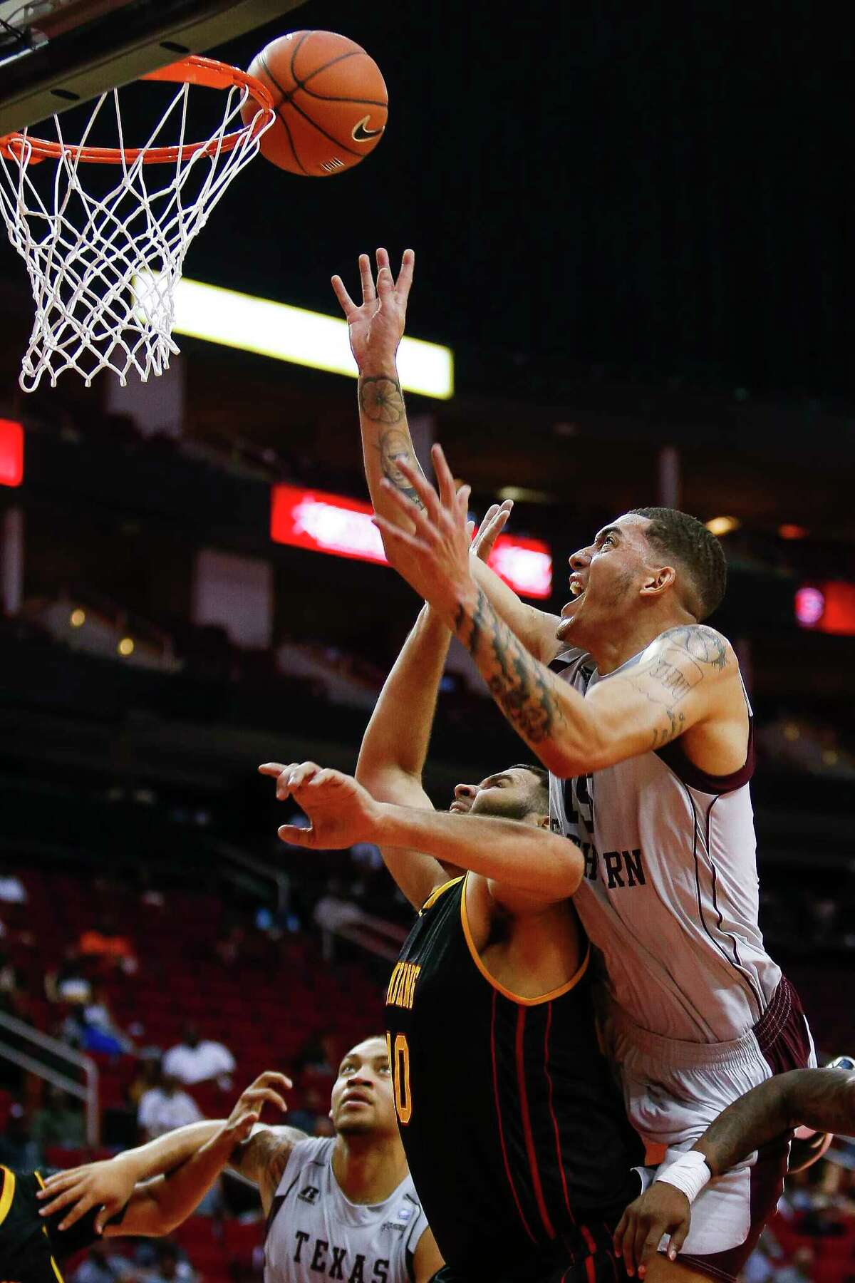 Texas Southern Tigers forward Stephan Bennett (15) puts a rebound back into the basket over Grambling State Tigers center Noah Cummings (40) as the Texas Southern Tigers take on the Grambling State Tigers during the SWAC Basketball Tournament semifinals at the Toyota Center Friday, March 10, 2017 in Houston.