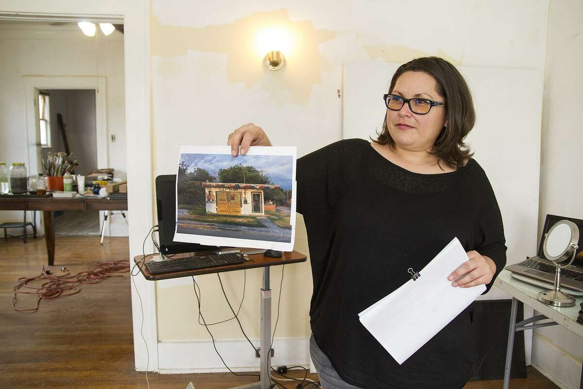 Fernandez holds up one of the photos she uses to create her paintings.
