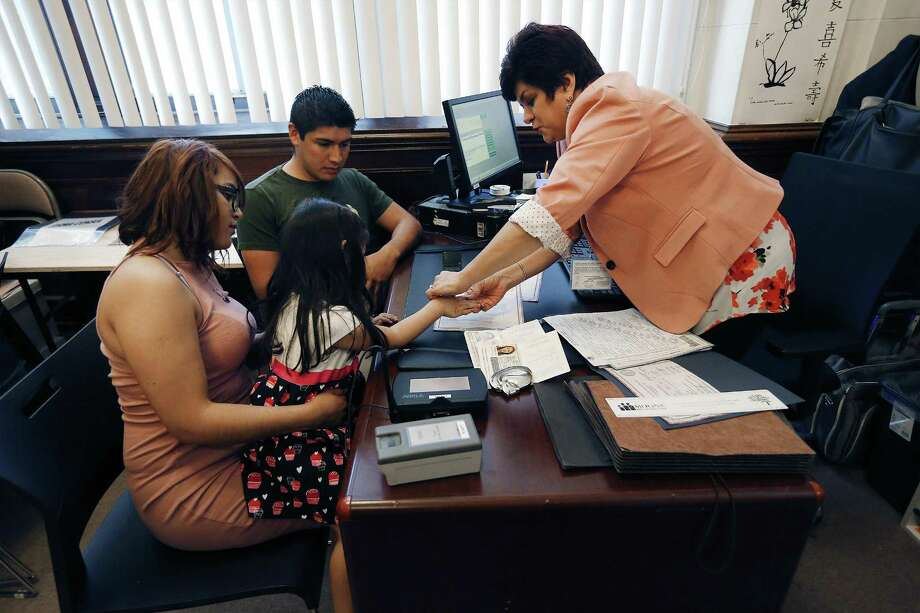 Guadalupe Bear Gasca (right) of the Mexican Consulate in San Antonio helps Yesenia Torres and her three-year-old daughter, Dafne Ruiz, make in a thumbprint of the young girl on a birth certificate document on Friday, Mar. 10, 2017, as Torres' husband Daniel Ruiz looks on. The consulate's office will start issuing birth certificates which makes it easier for those who came here without papers to get ID documents. Carlos Manuel Sada, Mexico Undersecretary of Foreign Affairs, marked the occasion by presenting the first birth certificate processed in the San Antonio office to the family at a press event. (Kin Man Hui/San Antonio Express-News) Photo: Photos By Kin Man Hui / San Antonio Express-News / ©2017 San Antonio Express-News