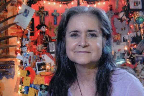 Mary Cerruti poses with a tribute she created for her parents as part of the annual Day of the Dead celebration at Casa Ramirez, a store where she occasionally worked. The store owners estimate the photo was taken around 2010. The basket contains images of her parents, a wood folk art skeleton, marigolds and small candles.