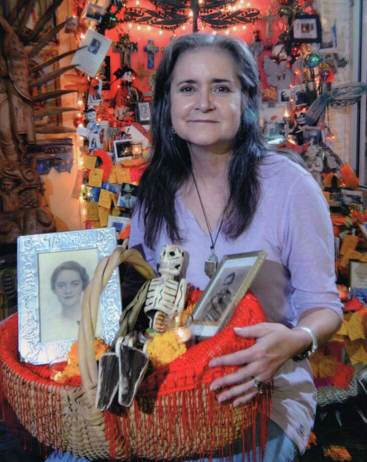 Mary Cerruti poses with a tribute she created for her parents as part of the annual Day of the Dead celebration at Casa Ramirez, a store where she occasionally worked. The store owners estimate the photo was taken around 2010. The basket contains images of her parents, a wood folk art skeleton, marigolds and small candles. Photo: Agapito Sanchez For Casa Ramirez, Courtesy Of Casa Ramirez