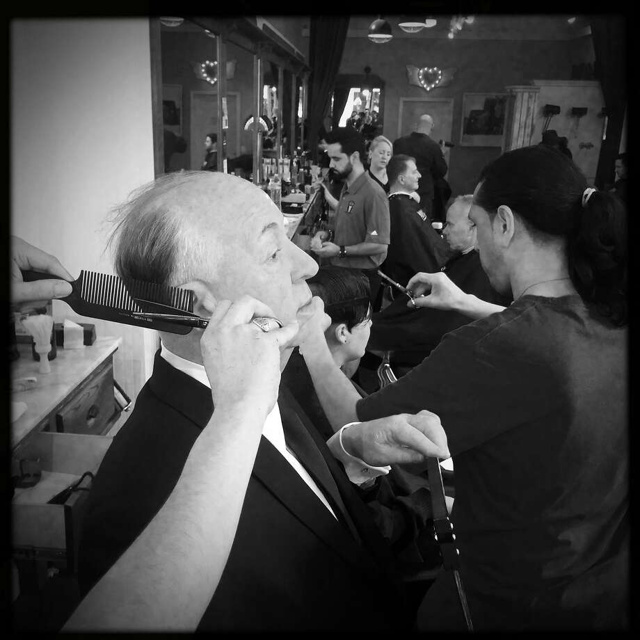 As Michael Casias (right) styles Joanna Pluhowski's hair, David Garcia pretends to trim the hair of a wax figure of Alfred Hitchcock that Madame Tussaud's brought to Peoples Barber in San Francisco, Calif., on Friday, March 10, 2017. Photo: Scott Strazzante, The Chronicle
