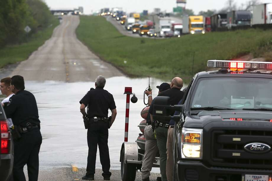 Traffic backs up as officials in Guadalupe County search floodwaters Friday March 10, 2017 after a person was reportedly rescued near Santa Clara Creek at the access road of Interstate 10 at exit 599 near Marion, Texas. Photo: John Davenport, STAFF