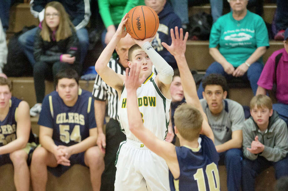 BRITTNEY LOHMILLER | blohmiller@mdn.net Dow's Ben Zeitler prepares to shoot for three points while being defended by Mount Pleasant's Noah Ingram in the first half of the Class A district finals at Bay City Central Friday evening. Mount Pleasant defeated Dow 44-35. / Midland Daily News