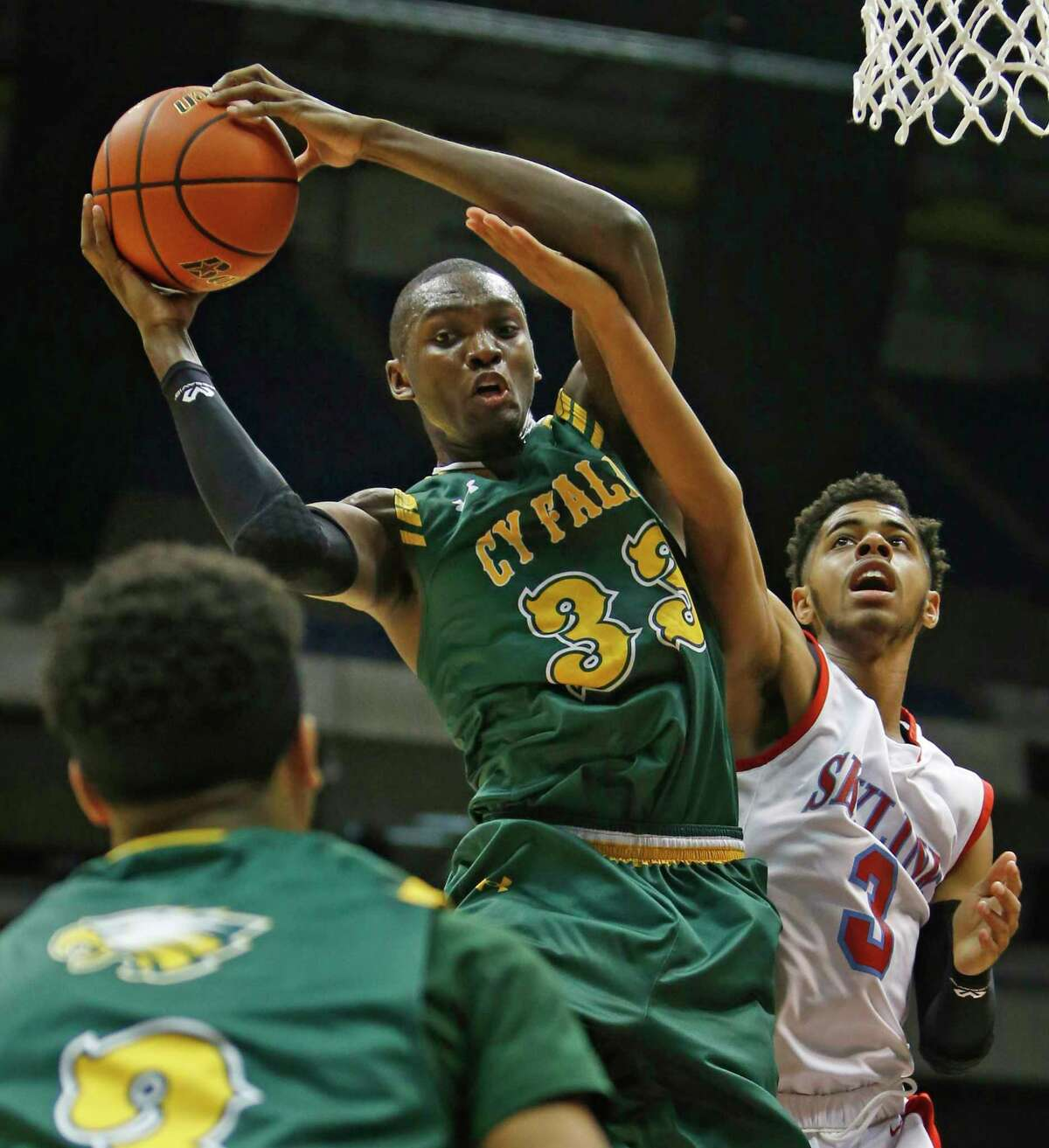 Deshang Weaver of Cypress Falls grabs a rebound next to Dallas Skyline's Jase Townsend during the Class 6A boys basketball semifinal Friday night.