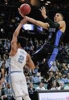 Duke's Jayson Tatum soars over North Carolina's Joel Berry II to score two of his 24 points Friday.