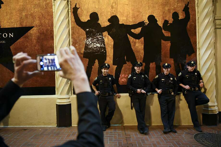Bet Darwin of Ohio takes a picture of a group of San Francisco Police Officers as they stand in front of Hamilton sign before the plays first public performance at the Orpheum Theater in San Francisco, CA, on Friday March 10, 2017.Scroll through the gallery for sights from the performance. Photo: Michael Short, Special To The Chronicle