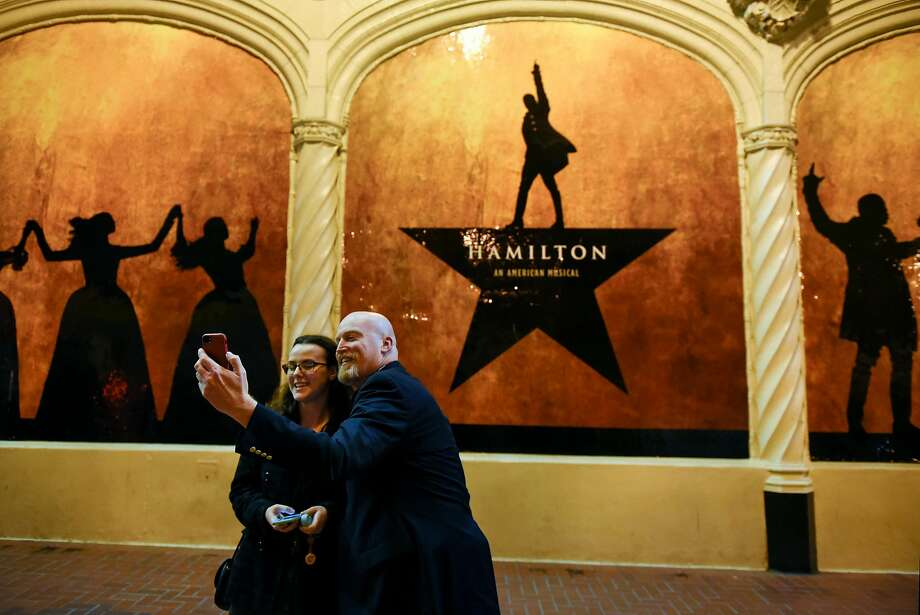 Emma and James Pixton of Alameda take a picture in front of a Hamilton sign before the plays first public performance at the Orpheum Theater in San Francisco, CA, on Friday March 10, 2017, Photo: Michael Short, Special To The Chronicle