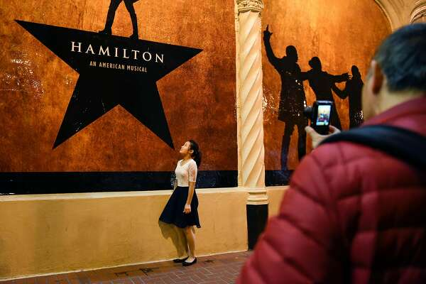 People take pictures in front of Hamilton signs before the plays first public performance at the Orpheum Theater in San Francisco, CA, on Friday March 10, 2017,