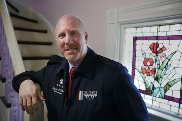 OutVets founder Bryan Bishop poses in his house in Boston, Friday, March 10, 2017.  The organizers of Boston's embattled St. Patrick's Day parade have scheduled an emergency meeting to reconsider their vote to shut out the gay veterans group. This week's decision to bar OutVets from marching drew immediate condemnation from high-profile politicians and stirred up a furor on social media. (AP Photo/Michael Dwyer)