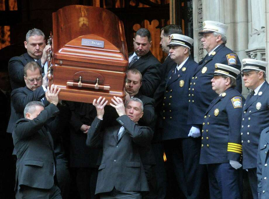 Acting Fire Chief Antonio Conte stands at the top of the stairs along with the Stamford firefighters as the caskets are carried out at the end of the funeral for the three Badger sisters, Lilian, Sarah and Grace, at St. Thomas Church Fifth Avenue in Manhattan, N.Y., on Thursday, January 5, 2012. The sisters were killed along with their grandparents, Lomer and Pauline Johnson, when their Stamford, Conn. home burned down on Christmas Day. Photo: Keelin Daly / Keelin Daly / Stamford Advocate