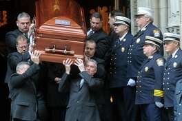 Acting Fire Chief Antonio Conte stands at the top of the stairs along with the Stamford firefighters as the caskets are carried out at the end of the funeral for the three Badger sisters, Lilian, Sarah and Grace, at St. Thomas Church Fifth Avenue in Manhattan, N.Y., on Thursday, January 5, 2012. The sisters were killed along with their grandparents, Lomer and Pauline Johnson, when their Stamford, Conn. home burned down on Christmas Day.