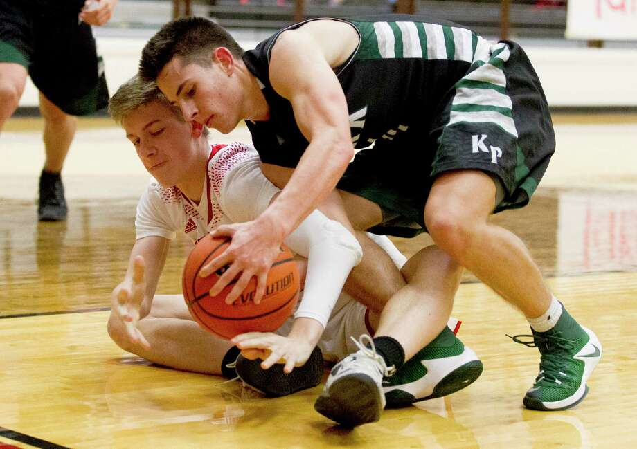 Porter forward Trvor Benson (20) and Kingwood Park guard Colton Killian (4) battle for control of a loose ball during the fourth quarter of a District 21-5A boys high school basketball game at Porter High School Friday, Dec. 9, 2016, in Porter. Kingwood Park defeated Porter 62-49. Photo: Jason Fochtman, Staff Photographer / Houston Chronicle