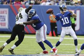 New York Giants quarterback Eli Manning (10) throws a pass as New Orleans Saints' Cameron Jordan (94) rushes past New York Giants' Marshall Newhouse (73) during the first half of an NFL football game Sunday, Sept. 18, 2016, in East Rutherford, N.J.  (AP Photo/Seth Wenig)