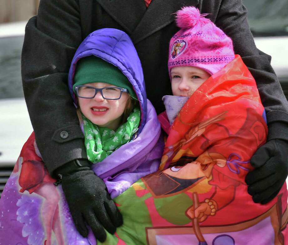 Bundled up and warm in their father's arms, sisters Elizabeth, 7, and Veronica Scaringe, 8, of Albany, watch the annual the Limericks North Albany St. Patrick's Parade Saturday March 11, 2017 in Albany, NY.  (John Carl D'Annibale / Times Union) Photo: John Carl D'Annibale / 20039896A