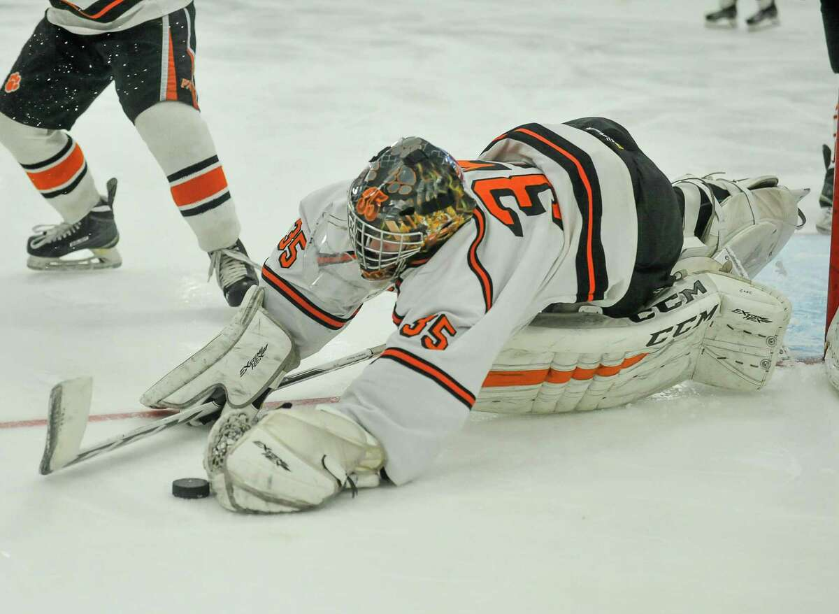 Ridgefield goalie Sean Keegans dives for the puck for one of his 39 saves Saturday agianst Fairfield Prep.