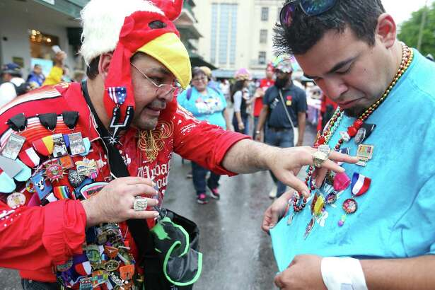 Paul Gonzales (left) and Adam Rocha trade Fiesta medals at Pin Pandemonium part of the Fiesta Fiesta at the Alamo event, the official opening of Fiesta Thursday April, 16, 2015.