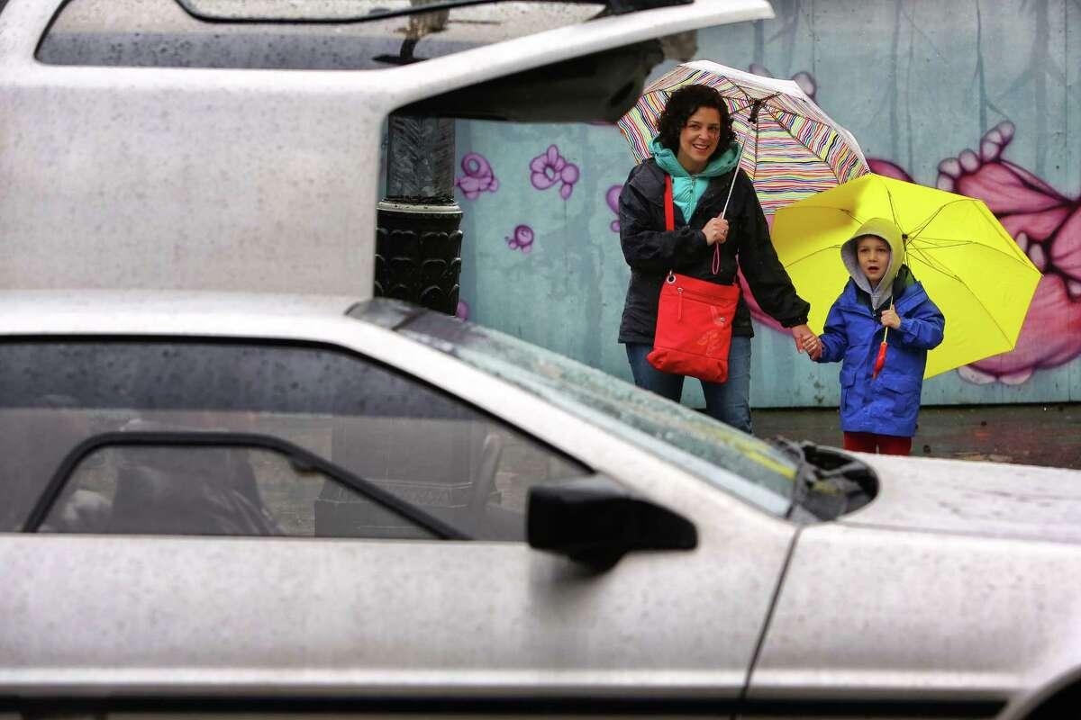 April Kristjansson and her son Owen, 5, watch as the Pacific Northwest DeLorean Club drives past.