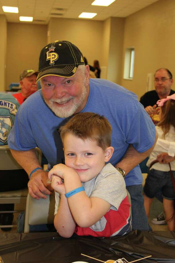 Brent Johnston, the father of Liberty County Pct. 1 Constable Justin Johnston, is pictured with Brodee Bryan, 4, of Liberty. According to Bryan's parents, Bradley and Misty Bryan, the boy, after hearing about the accident that injured the constable, took money from his own piggy bank to buy food items at Johnston's benefit on Saturday, March 11. Photo: Vanesa Brashier
