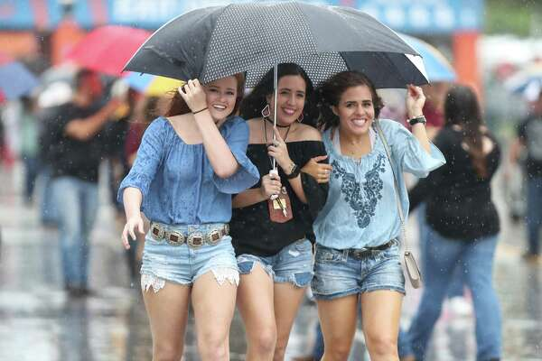 Steady rain didn't keep Bailey Bryant (left-right), Alex Gonzales and Annie Kitchen from attending the Houston Livestock Show and Rodeo Saturday, March 11, 2017, in Houston.