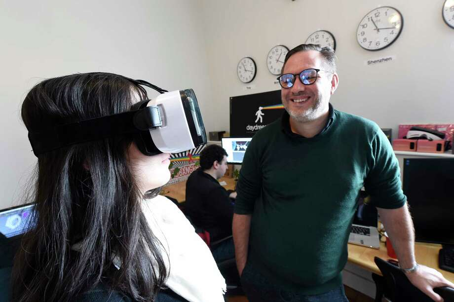 Courtney Yasuda, left looks in to a virtual reality mask as V. Owen Bush, co-founder and CEO of SpaceoutVR looks on in their offices at newly renovated Quackenbush building Thursday  March. 9, 2017 in Troy, N.Y. (Skip Dickstein/Times Union) Photo: SKIP DICKSTEIN / 20039915A