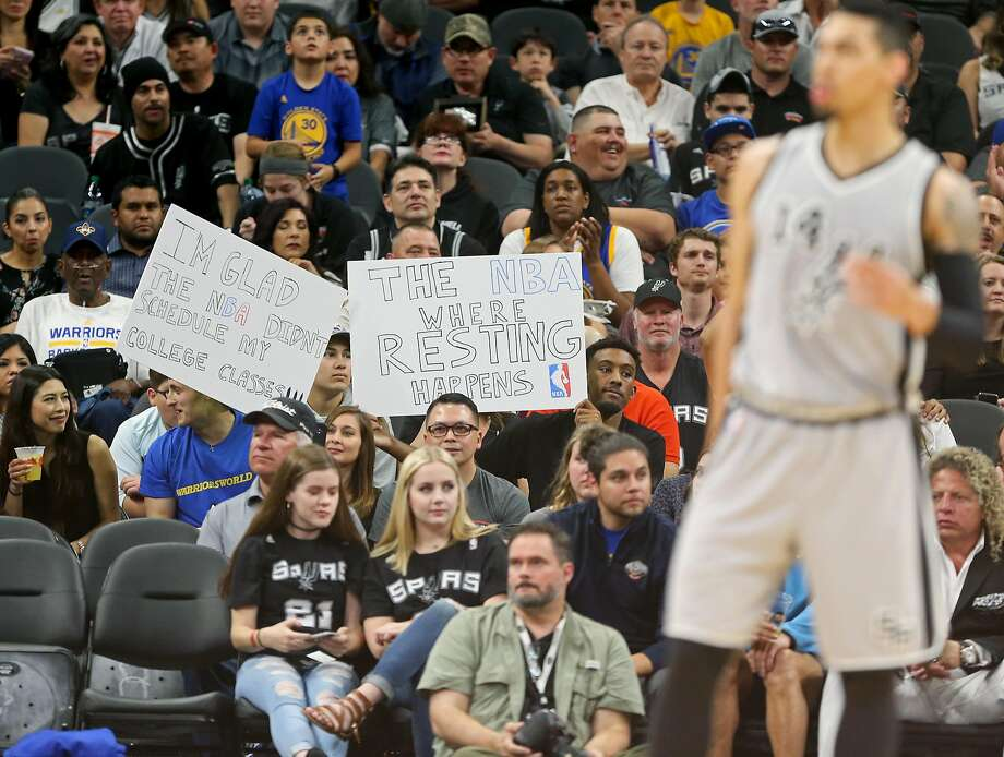 Dustin Lindner (left) and Theo Duplechain at the Warriors Spurs game hold a sign stating fans' feelings about a night off. Photo: Edward A. Ornelas, San Antonio Express-News
