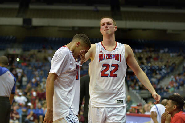 Brazosport junior center Hunter Quick (22) walks over to console teammate and senior guard Chris Rossow after Rossow fouled out of the game during the waning moments of their Class 4A state final versus Silsbee at the Alamodome in San Antonio on Saturday, March 11, 2017. (Photo by Jerry Baker/Freelance)