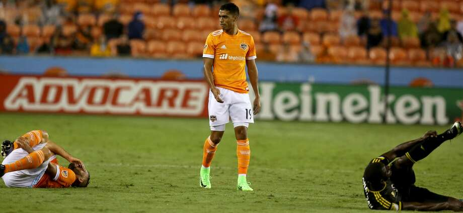 Houston Dynamo forward Mauro Manotas (19) watches Dynamo midfielder Alex (14) and Columbus Crew defender Jonathan Mensah (4) in pain on the grounds during the second half of the MLS soccer game at BBVA Compass Stadium Saturday, March 11, 2017, in Houston. Mensah got a red card for fouling on Alex during this play. The Dynamos defeated the Crews 3-1. ( Yi-Chin Lee / Houston Chronicle ) Photo: Yi-Chin Lee/Houston Chronicle