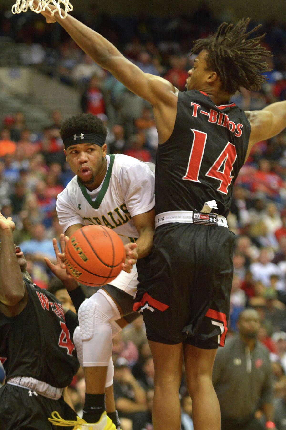 Cy Falls junior guard Trajan Wesley looks to dish the ball on a drive against San Antonio Wagner's Justice Tolbert (14) during the 2nd quarter of their Class 6A state final at the Alamodome in San Antonio on Saturday, March 11, 2017. (Photo by Jerry Baker/Freelance)