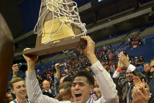 Cy Falls head coach Richard Flores, center, hoists the Eagle's trophy after their 63-57 win over San Antonio Wagner in their Class 6A state final at the Alamodome in San Antonio on Saturday, March 11, 2017. (Photo by Jerry Baker/Freelance)