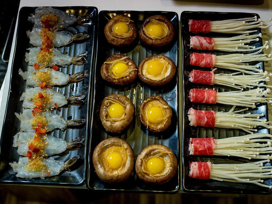 Shrimp with garlic (left), quail eggs with mushrooms, and rolled beef with enoki mushrooms before cooking at Tastee Steam Kitchen in Oakland. Photo: John Storey, Special To The Chronicle