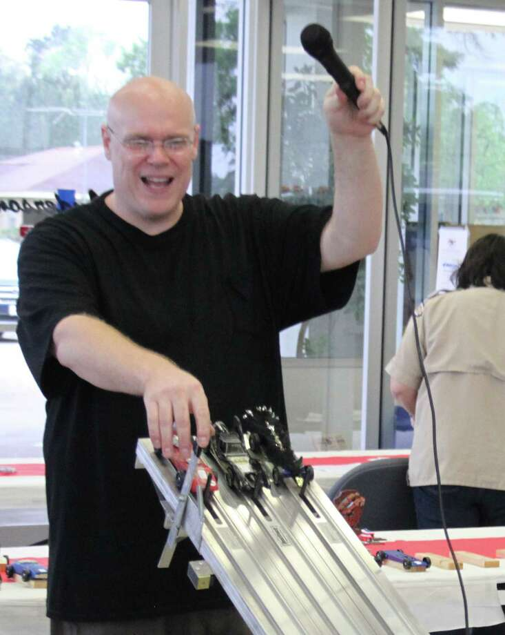Volunteer Stephen Huff prepares three cars for the Trinity District Boy Scout Pinewood Derby held at Anderson Ford on March 11. Photo: Jacob McAdams