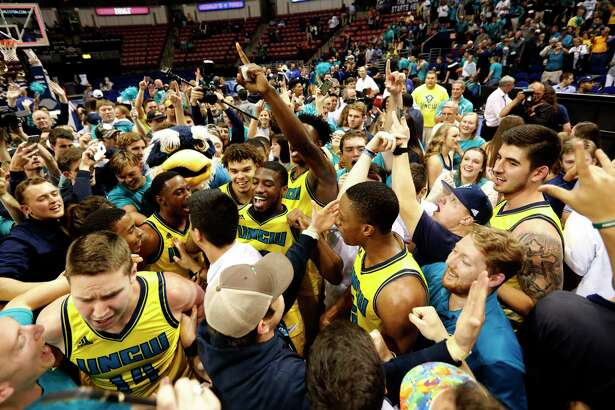 UNC Wilmington players, coaches and fans storm the court after defeating College of Charleston 78-69 at the end of an NCAA college championship basketball game in the Colonial Athletic Association tournament at the North Charleston Coliseum in North Charleston, S.C., Monday, March 6, 2017. (AP Photo/Mic Smith)