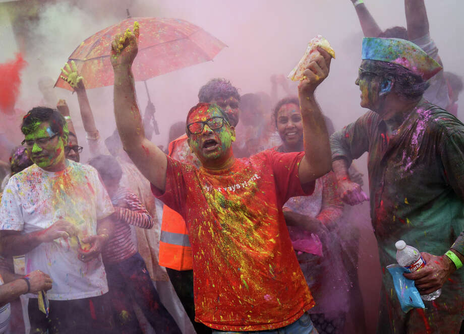 Raju Veludandi dances and throws colored powder with fellow Holi festival attendees on Saturday, March 11, 2017, at the Hindu Temple of The Woodlands. Photo: Michael Minasi/Houston Chronicle