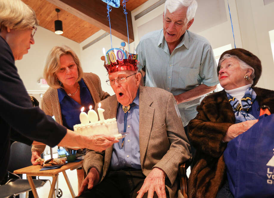 The Woodlands resident Warren Johnson blows out his birthday candles while surrounded by his daughter Susan Davis, left, his nephew Tim Tye, center, and his girlfriend Joan Brown, right, during his 100th birthday celebration on Sunday, March 12, 2017, at The Woodlands Community Presbyterian Church. Photo: Michael Minasi, Staff Photographer / © 2017 Houston Chronicle